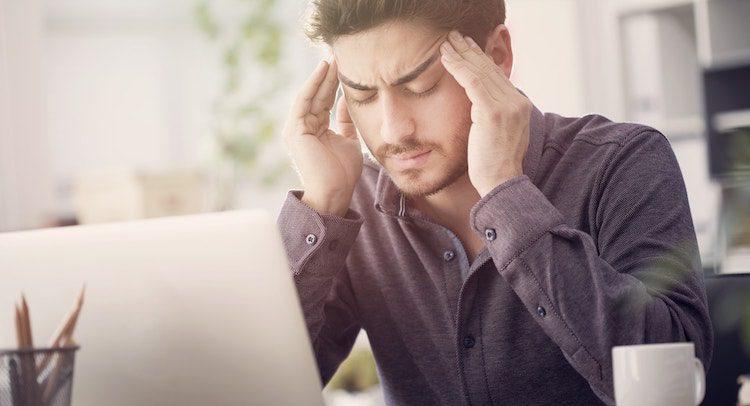 Homme se massant la tête devant son ordinateur en raison d'une migraine