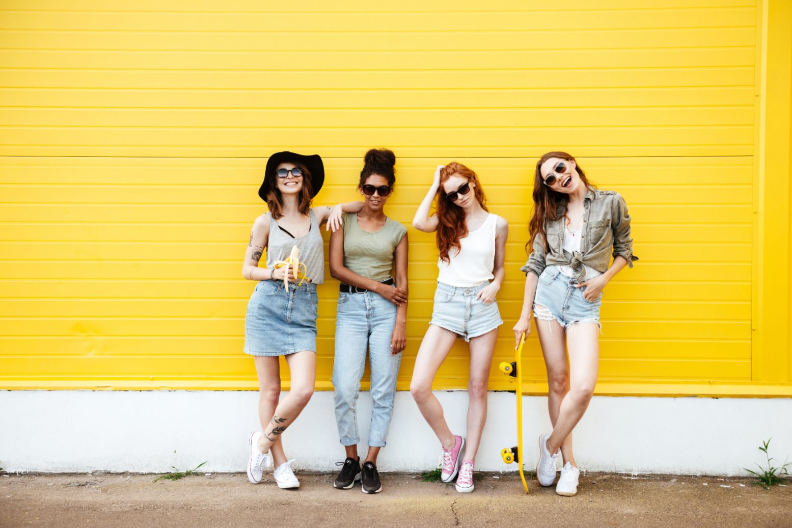 Young smiling women friends standing over yellow wall